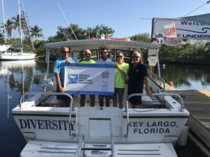 World Ocean Day - Island Ventures crew holding NOAA Clean Seas Banner on back of their boat Diversity