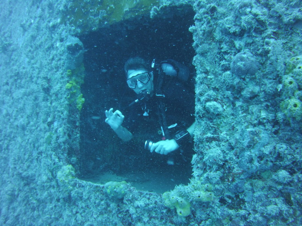 Diver exiting the wreck of the Spiegel Grove wreck in Key Largo Florida where the water is deep blue