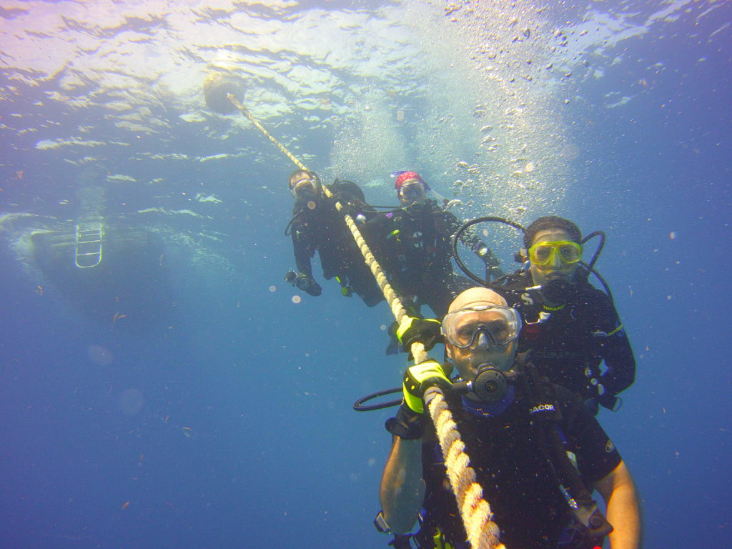 SCUBA Divers hanging on line on underwater safety stop