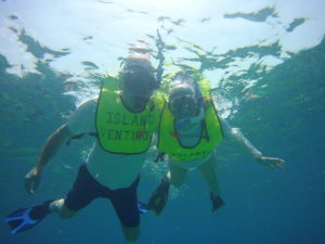 two snorkelers in the water. Shot is taken from below the snorkelers and they have their faces in the water looking down