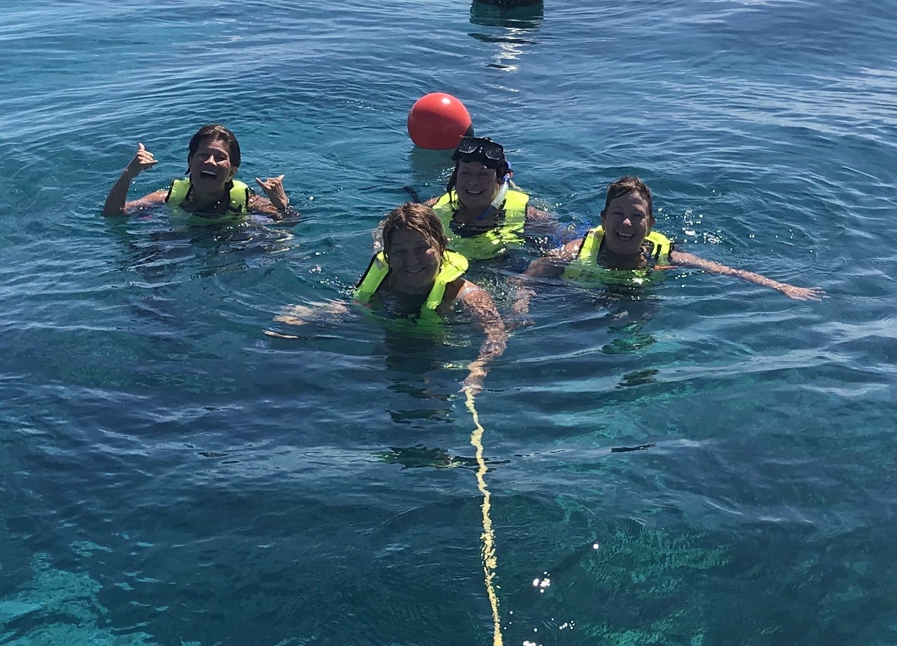 Snorkelers on tag line in blue water