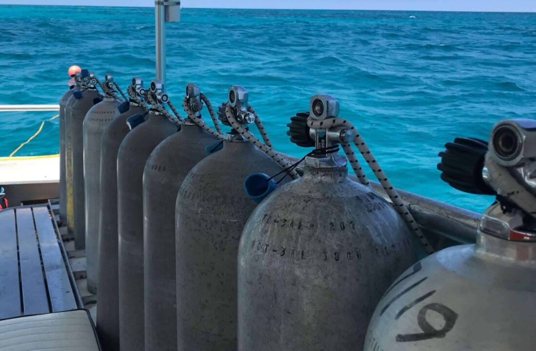 SCUBA Tanks on boat at sea on reef. The tanks stand in a line with the backdrop of the blue sea